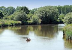 Schilf und hohe Bäume am Ufer der Oste - ein Kanu fährt auf dem Fluss.