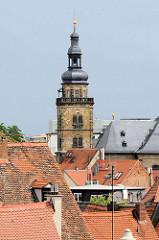 Kirchturm der St. Martinskirche zwischen den Ziegeldächern der Stadt Bamberg.