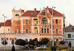 Architektur in Mosonmagyaróvár, Ungarn - Wohnhaus mit hoher Mauer umgeben. Turm mit Zinnen, Ziegelfassade.
