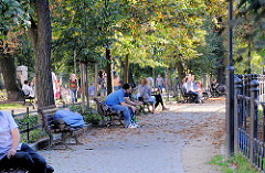 Grünanlage in Wroclaw, Breslau - Parkbesucher sitzen oder liegen auf Parkbänken in der Abendsonne.