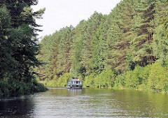 Hohe Tannen an den Ufern der Elde-Müritz Wasserstrasse - ein Sportboot fährt am Ufer entlang.