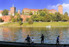 Angler und Jogger am Ufer der Weichsel - Wisla; Blick über den Fluss zur Wawel - Burgmauern und Türme der Kathedrale St. Stanislaus und Wenzel in Krakau / Kraków.