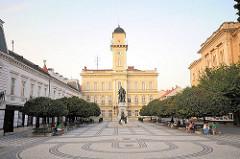 Rathaus und Rathausplatz mit Bäumen und Bänken in Komarno / Slowakei an der Donau.