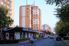 Wohnblocks mit Geschäften - Fahrradfahrerin; Fotos aus der Stadt Mosonmagyaróvár, Ungarn.