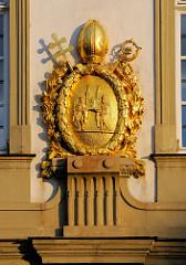 Schmuck Hausfassade - vergoldetes Stuckdekor; König Heinrich II. und Kunigunde tragen den Bamberger Dom