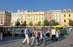 Hauptmarkt in Krakau - Touristen gehen über den Platz - historische Architektur.