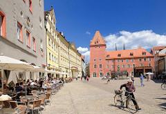 """Cafés in der Sonne am Haidplatz in Regensburg - im Hintergrund die """"Neue Waag"""", Patrizierhaus von 1441."""