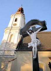 Kreuzigungsszene vor der St. Mauritiuskriche in Breslau, Wroclaw - Christus am Holzkreuz, Kirchturm der gotischen Kirche.