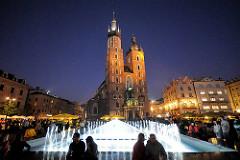Marktplatz mit Springbrunnen am Abend - Nachaufnahme, beleuchtete Türme des Krakauer Wahrzeichens die Marienkirche.