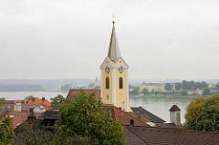 Ein Kirchturm ragt über den Dächern empor - im Hintergrund der Lauf der Donau.