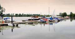 Sportboothafen an der Eider - Bootssteg mit Motorbooten und Segelschiffen - Sportboothafen Süderstapel.