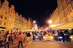 Nachtaufnahme Grosser Ring, Rynek in Wroclaw / Breslau - Touristen gehen am Abend über den Marktplatz oder sitzen im Freien in Restaurants unter Markisen.