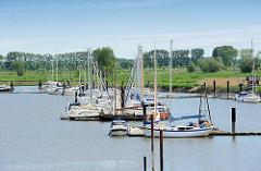 Sportboothafen Borsfleth an der Störmündung - die Motorboote und Segelschiffe liegen geschützt am Steg. Das sogenannte Störloch ist ein alter Arm der Stör und liegt hinter dem Sperrwerk.