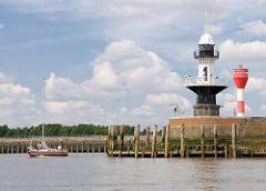 Leuchtfeuer an der Einfahrt zur Schleuse Nord-Ostsee-Kanal in Brunsbüttel - ein Sportboot, Segelboot verlässt die Schleusenkammer.