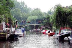 Gracht / Kanal in Friedrichstadt - Sportboote, Motorboote sind am Ufer festgemacht.