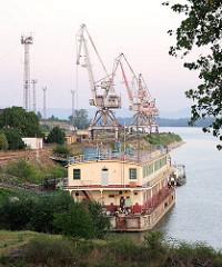 Wohnschiff und Hafenkräne - in Komarno, Slowakei; im Hintergrund die Donau.