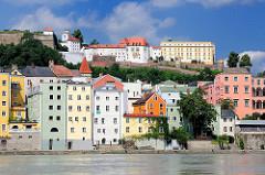 Blick auf die farbigen Hausfassaden der Wohnhäuser an der Innpromenade in Passau - im Hintergrund  die Veste Oberhaus auf der linken Seite der Donau auf dem St. Georgs Berg - gegründet 1219, Burg und Residenz des fürstlichen Bischofs vom Hochstift Pa