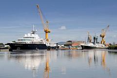 Werftanlagen an der Stör in Wewelsfleet - Schiffe liegen am Ausrüstungskai - Werftkräne stehen am Ufer.
