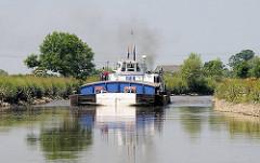 Schmale Fahrrinne - Schubschiff mit Schute auf der Pinnau in Fahrt Richtung Uetersen.
