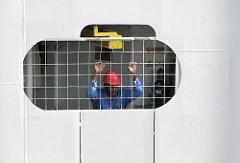 Ein Matrose / Arbeiter des  181 m langen und 25m breiten Kreuzfahrtschiff AZAMARA JOURNEY blickt durch eine vergitterte Öffnung  aus dem Schiff.