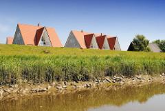 Moderne Wohnhäuser hinter dem Deich der Pinnau - die Fenster der Giebel überragen die Deichkrone des Flusses.