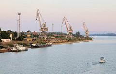 Blick über Hafenanlagen - Hafenkräne in Komarno, Slowakei - im Hintergrund die Donau.