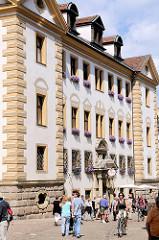 Fassade Altes Rathaus in Regensburg - Touristen und Einwohner in der Sonne auf der Strasse.