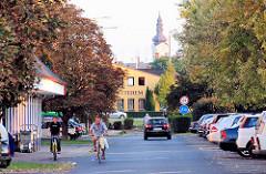 Strassenszene in Mosonmagyaróvár, Ungarn - im Hintergrund ein Kirchturm.