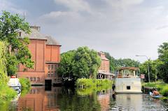 """Historische Industriearchitektur in Neu Kaliß - ehem. Mühlengebäude, jetzt Wasserkraftwerk. Ein Sportboot fährt Richtung Schleuse """"Findenwirunshier""""."""