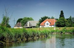Lauf der Pinnau vor Uetersen - Wohnhäuser hinter dem Deich - Gras am Ufer vom Fluss.