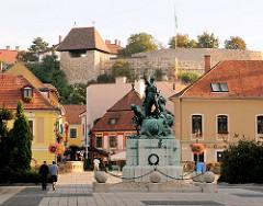 Blick zu den Burganlagen von Eger - davor  die Bronzstatue Dobó István auf dem Doboplatz.