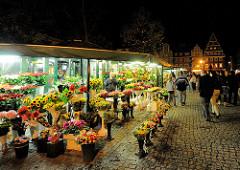 Beleuchteter Blumenstand mit bunten Blumen am Abend auf dem Marktplatz von Wroclaw, Polen.