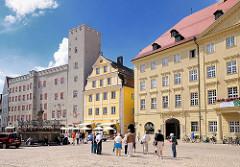 Haidplatz in Regensburg - lks. das Goldene Kreuz, Patrizierburg - Haus mit Zinnen und Turm. Rechts das klassizistische Thon Dittmer Palais - Touristen überqueren den Platz in der Sonne.