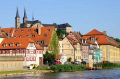 Historische Architektur am Ufer der Regnitz in Bamberg, mehrstöckige  Fachwerkhäuser. Hinter den Dächern die Klosterkirche St. Michael auf dem Klosterberg, Michelsberg.
