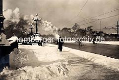 Hoher Schnee auf dem Fussweg der Lombardsbrücke in Hamburg; Güterzug.
