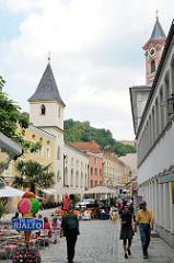 Lks. die  Spitalkirche St. Johannes der Täufer  - rechts der Kirchturm der Stadtpfarrkiche St. Paul - 1050 dem hl. Paulus geweiht - nach Zerstörung jetziger Bau 1678 fertig gestellt -  Rindermarkt in Passau.