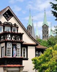 Wohnhaus mit Holzbalkon und Erker - blau rot gefasste Marienfigur - im Hintergrund die vier Türme des Kaiserdoms zu Bamberg.
