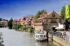 Blick auf die Regnitz in Bamberg - ein Fahrgastschiff liegt am Kai bei einem historischen Kran - dahinter das ehem. Schlachthaus.