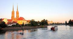 Die Oder in Wroclaw, Breslau am Abend - Motorboot und Raddampfer, Ausflugsschiff auf dem Wasser - die Türme des gotischen Doms / Kathedrale St. Johannes der Täufer werden von der Abendsonne angestrahlt.