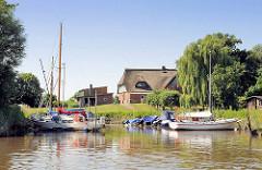Sportboothafen am Ufer der Krückau - im Hintergrund ein reetgedecktes Wohnhaus am Deich.