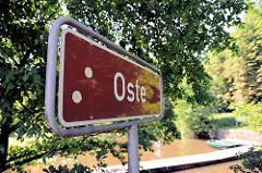 Schild Fluss Oste in Bremervörde - rotes Schild mit weisser Schrift.