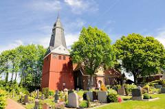 St. Nikolaikirche in Beidenfleth an der Stör - Friedhof mit Grabsteinen; Kirchenbau zwischen Bäumen.