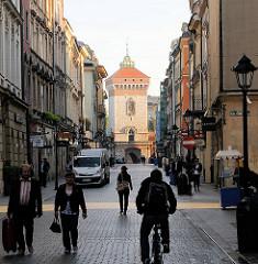 Enge Gasse in Krakau / Kraków - Fussgänger und Radfahrer; im Hintergrund der Turm des Floriantors.