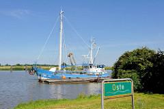 Schild Oste - grüner Grund mit weisser Schrift an der Oste bei Neuhaus - ein blauer Fischkutter liegt am Ufer.