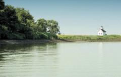 """Einfahrt Haseldorfer Binnenelbe - Bäume und Sträucher am Wasser - im Hintergrund der  1896 gebaute Leuchtturm von Julssand, der von Seglern auch """"Kleiner Kohn"""" genannt wird."""