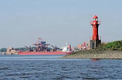 Leuchtfeuer auf der Elbinsel Pagensand - Einfahrt zur Pagensander Nebenelbe. Im Hintergrund Kaianlagen, Hafenanlagen und Frachtschiff auf der gegenüber liegenden Seite der Elbe in Bützfleth.