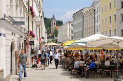 Blick in die Ludwigstrasse in der Stadt Passau - in der Fussgängerzone sitzen Touristen unter Sonnenschirmen in Cafés - im Hintergrund der Kirchturm der St. Michael, auch Studienkirche oder Jesuitenkirche genannt - Kirche des ehemaligen Jesuitenkolle