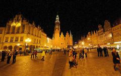 Marktplatz von Breslau / Wroclaw am Abend - Touristen gehen über das Kopfsteinpflaster auf dem Platz; im Hintergrund der Rathausturm und das historische Rathaus.