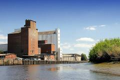 Industriearchitektur, Speichergebäude im Hafen von Itzehoe an der Stör; Schilf am Ufer des Flusses.