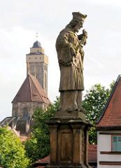 """Skulptur Hl. Johannes Nepomuk an der Oberen Brücke - im Hintergrund die Kirche """"Zu unserer lieben Frau"""" / Obere Pfarre."""
